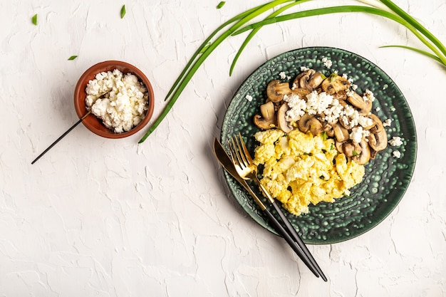Rührei mit pilzen und hüttenkäse auf vollweizentoast. leckeres frühstück oder snack auf einem leuchttisch, draufsicht.