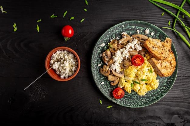 Rührei mit pilzen und hüttenkäse. leckeres frühstück oder snack auf einem dunklen tisch, draufsicht.