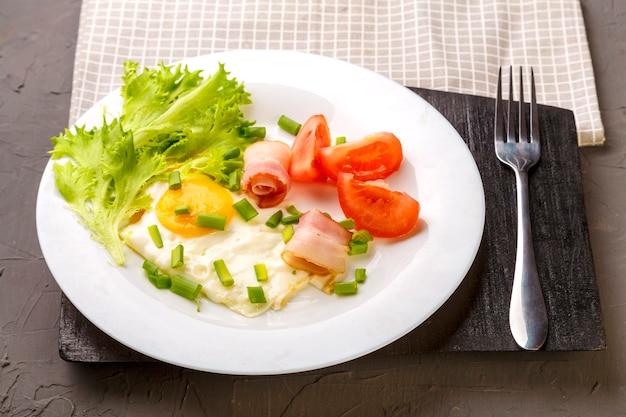 Rührei mit speck, garniert mit tomaten und frühlingszwiebeln und salat auf grauem betonhintergrund auf einem holzständer neben einer gabel