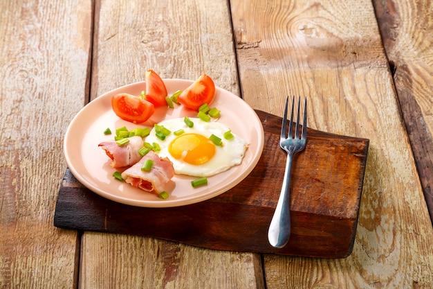 Rührei mit speck mit tomate und zwiebel auf einem holztisch in einem teller auf einem holzständer