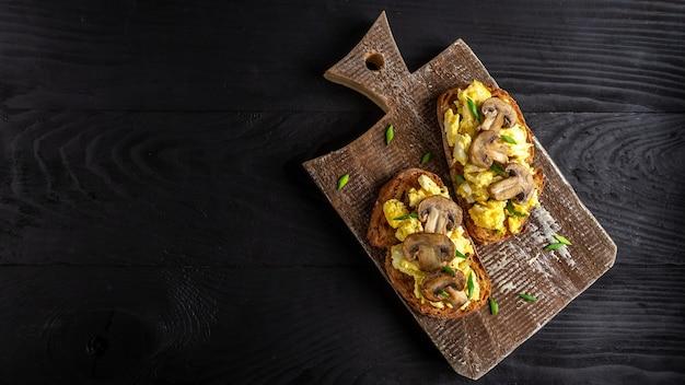 Rührei und pilze auf vollweizentoast. gesundes frühstück oder brunch.