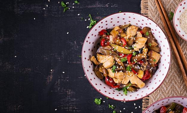 Rühren sie braten mit hühnchen, auberginen, zucchini und paprika - chinesisches essen. ansicht von oben, oben