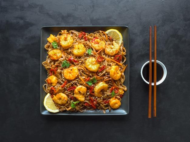 Rühren sie braten nudeln mit gebratenen garnelen, gemüse und sojasauce. asiatisches essen .