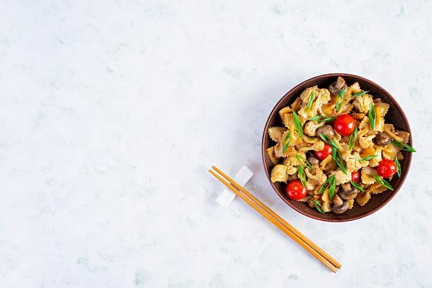Rühren sie braten nudeln mit gemüse, blumenkohl und pilzen. draufsicht