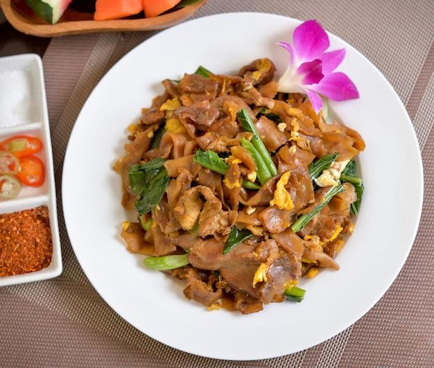 Rühren sie gebratene flache nudeln und schweinefleisch mit dunkler sojasauce (thailänder genannt pad see ew)