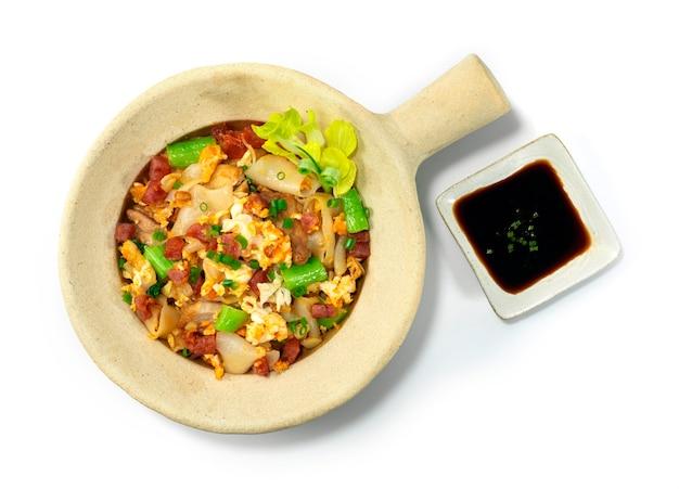 Rühren sie gebratene reisnudeln mit huhn im tontopf thai food fusion asian style draufsicht