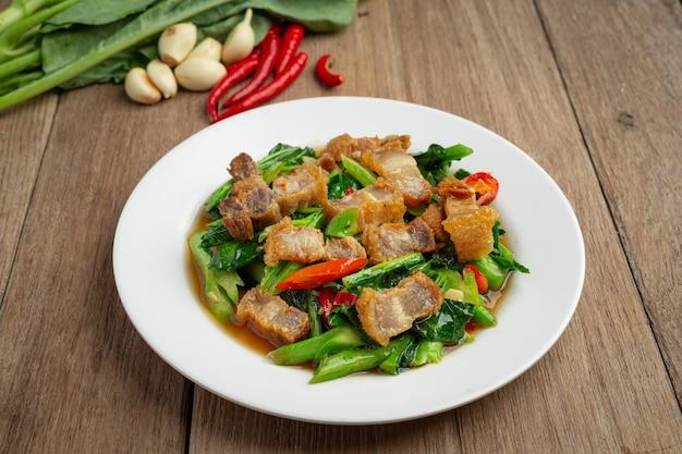Rühren sie gebratenen grünkohl, würziges knuspriges schweinefleisch auf thailändischem lebensmittelkonzept des holztischs.