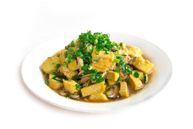 Rühren sie gebratenen tofu mit dem schweinefleisch und shitake mashroom auf die oberseite mit der seitenansicht der frühlingszwiebel- und soßensoße-thailändischen art lokalisiert