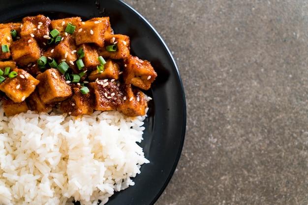 Rühren sie gebratenen tofu mit scharfer soße auf reis