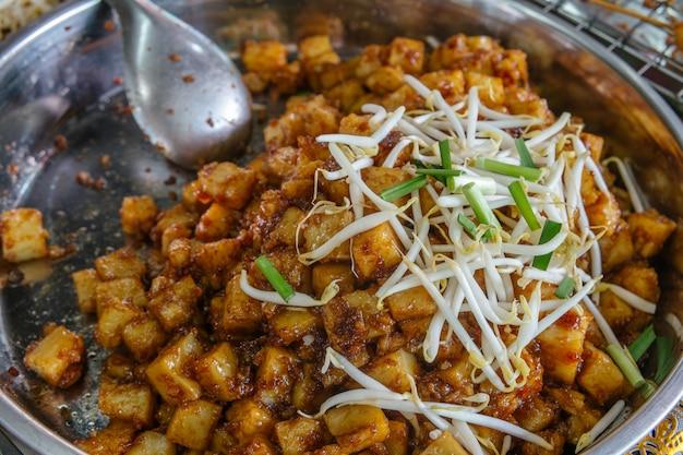 Rühren sie gebratenen weißen rettich oder rübenkuchen für verkauf am lebensmittelmarkt in bangkok