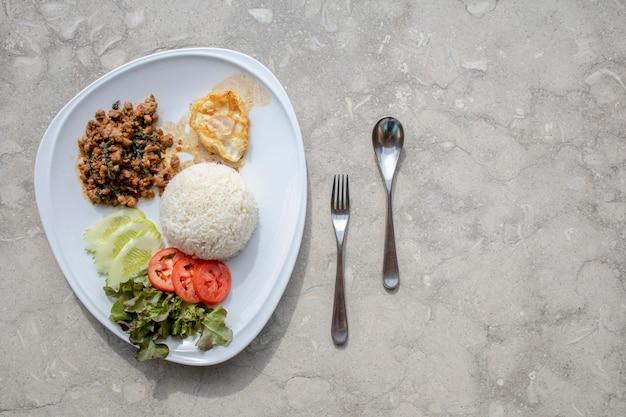 Rühren sie gebratenes basilikum mit reis und spiegelei traditionelles thailändisches essen