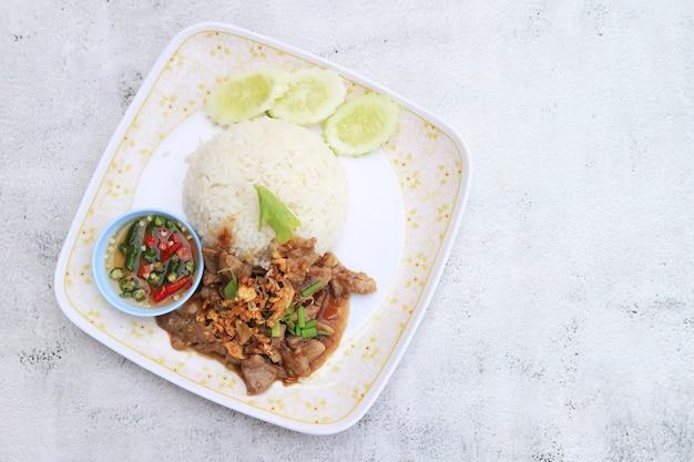 Rühren sie gebratenes knoblauchschweinefleisch mit reis lieblingsmenü und schnell zum kochen in thailand