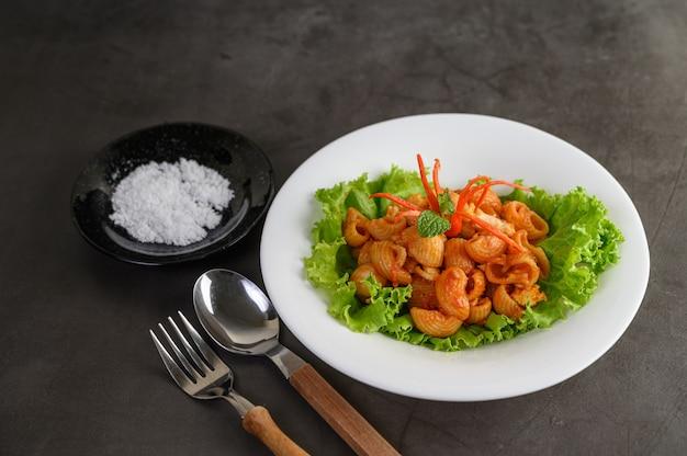 Rühren sie gebratenes makkaroni mit tomatensauce und schweinefleisch