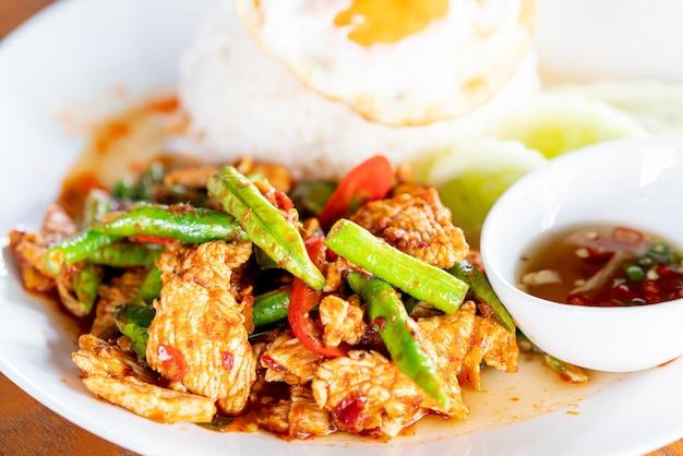 Rühren sie gebratenes schweinefleisch in roter curry-paste mit reis und spiegelei