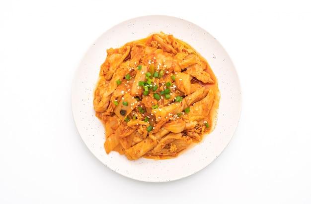 Rühren sie gebratenes schweinefleisch mit dem kimchi, das auf weiß lokalisiert wird