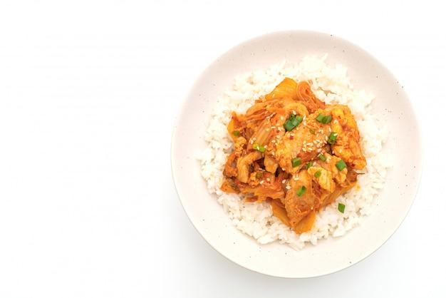 Rühren sie gebratenes schweinefleisch mit kimchi auf dem überstiegenen reis, der auf weißem hintergrund lokalisiert wird