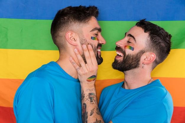 Rührende freunde des homosexuellen mannes stellen auf lgbt-mehrfarbiger flagge gegenüber