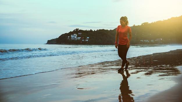 Rüttelndes training der frau auf dem strand morgens