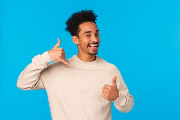 Ruf mich später an, baby. freche und kokette afroamerikaner zuversichtlich macho kerl mit schnurrbart, afro-haarschnitt zeigt daumen hoch und telefon geste, wink und lächelt flirty, blaue wand