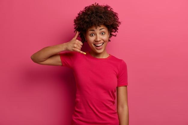 Ruf mich später an. frohe dunkelhäutige junge frau macht telefongeste, sieht positiv mit ansprechendem ausdruck aus, lächelt breit, in freizeitkleidung gekleidet, isoliert über rosiger wand. körpersprache