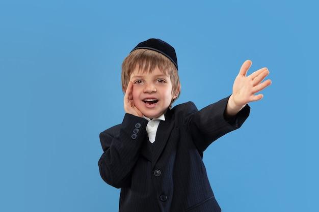 Rufen, schreien. porträt eines jungen orthodoxen jüdischen jungen lokalisiert auf blauer wand.