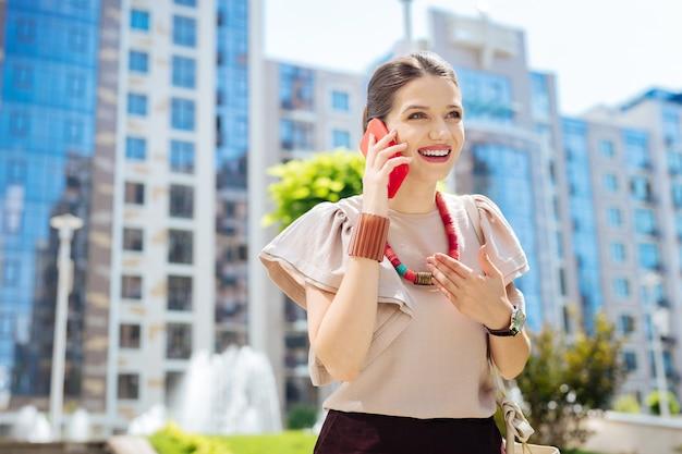Rufen sie einen freund an. positive nette frau, die lächelt, während sie ihr gespräch am telefon genießt