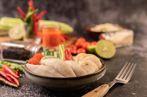 Rugby-fischbällchen mit zitronen-chili-paste, tomate und chili.