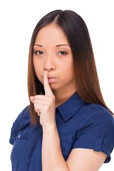 Ruhe! attraktive junge asiatin, die in die kamera schaut und den finger auf die lippen hält