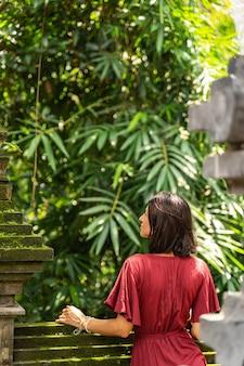 Ruhe bewahren, ruhig bleiben. nette junge frau, die in der nähe von steinstützen steht und große palmen betrachtet