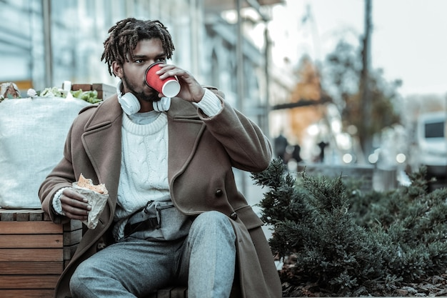 Ruhe dich aus. konzentrierter mann, der beiseite schaut, während er unter freiem himmel zu mittag isst