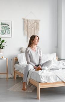 Ruhe dich nach einem anstrengenden arbeitstag aus. schöne junge lächelnde geschäftsfrau im pyjama, die kaffee trinkt und wegschaut, während sie auf einem bett in einem weißen raum sitzt.
