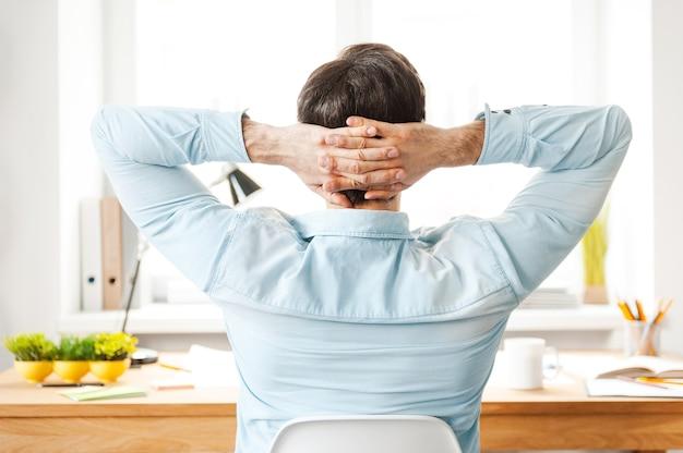 Ruhe für produktive arbeit. rückansicht eines jungen mannes im hemd, der den kopf in den händen hält, während er an seinem arbeitsplatz sitzt