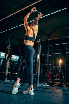 Ruhe. junge muskulöse frau, die im fitnessstudio mit den gewichten übt