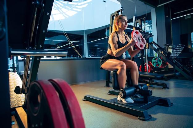Ruhe. junge muskulöse kaukasische frau, die im fitnessstudio mit den gewichten übt. sportliches weibliches modell, das kraftübungen macht, ihren oberkörper, hände trainiert. wellness, gesunder lebensstil, bodybuilding.