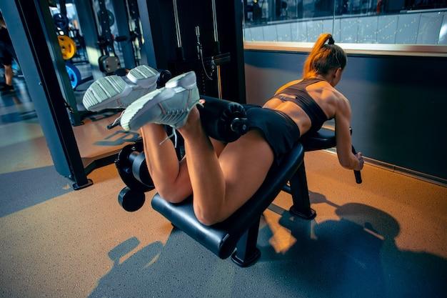 Ruhe. junge muskulöse kaukasische frau, die im fitnessstudio mit den gewichten übt. sportliches weibliches modell, das kraftübungen macht, ihren unterkörper, beine trainiert. wellness, gesunder lebensstil, bodybuilding.