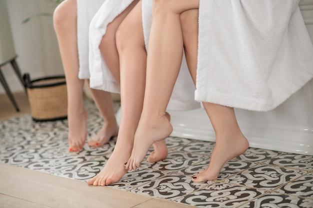 Ruhe, leichtigkeit. gepflegte nackte füße mit pediküre, die den boden berührt, in mustern von frauen, die ihre freizeit im spa verbringen, ohne gesicht