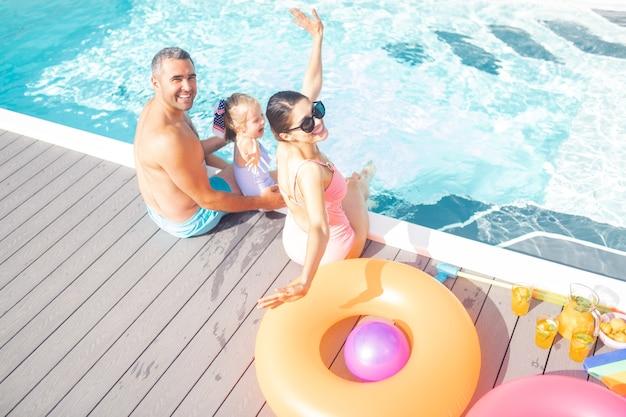 Ruhen in der nähe des pools. glückliche eltern und eine schöne tochter, die sich fröhlich in der nähe des pools ausruht?