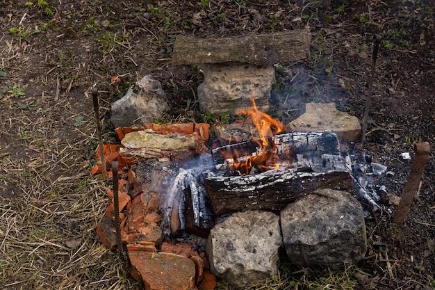 Ruhen sie sich im garten in der natur aus, bereiten sie ein feuer zum grillen vor, feuer aus kirschholz