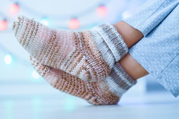 Ruhende frau in warmen, gestrickten, weichen, bequemen socken im winter zu hause.