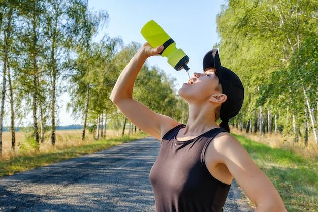 Ruhende junge frau trinkt nach hartem training wasser aus einer plastikflasche