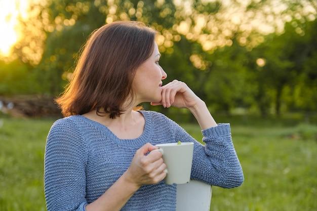 Ruhende reife frau mit tasse tee, weiblich in der natur, rustikaler landhausstil, sonnenuntergang des frühlingssommertages