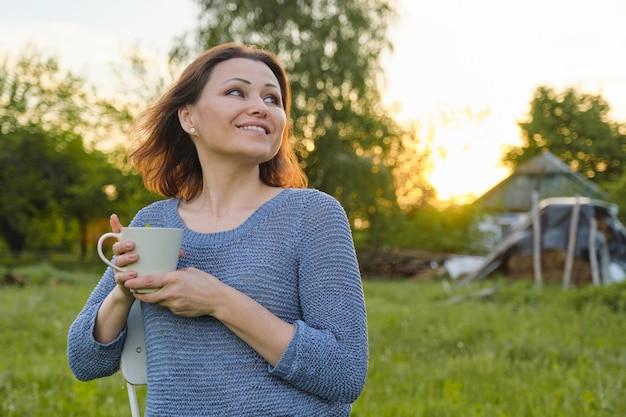 Ruhende reife frau mit tasse tee, weiblich in der natur
