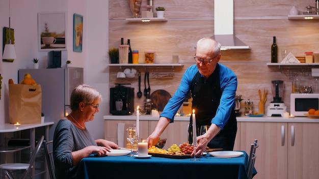 Ruhestand reifer mann überleben abendessen in einem esszimmer. älteres altes ehepaar, das spricht, am tisch in der küche sitzt, das essen genießt, ihr jubiläum mit gesundem essen feiert.