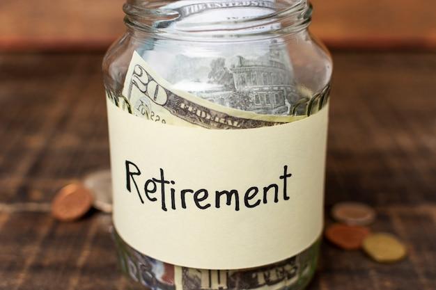 Ruhestandsaufkleber auf einem glas gefüllt mit geld