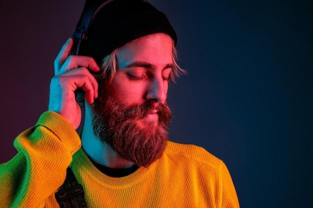 Ruhig, glücklich. porträt des kaukasischen mannes auf gradientenstudiohintergrund im neonlicht. schönes männliches modell mit hipster-stil in kopfhörern. konzept der menschlichen emotionen, gesichtsausdruck, verkauf, anzeige.