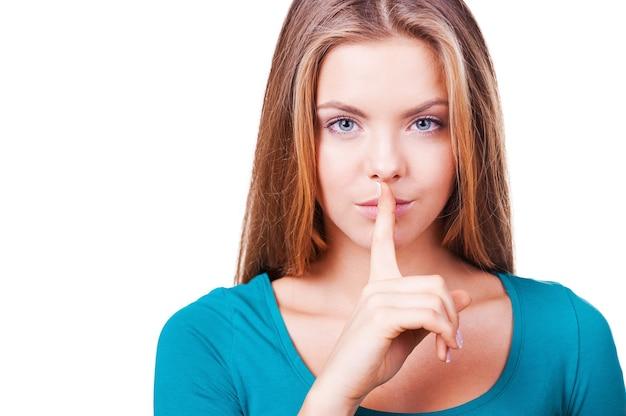 Ruhig sein! nahaufnahme einer attraktiven jungen frau, die in die kamera schaut und den finger auf die lippen hält, während sie isoliert auf weiß steht