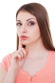 Ruhig sein! schöne junge frau, die in die kamera schaut und den finger auf die lippen hält, während sie isoliert auf weiß steht