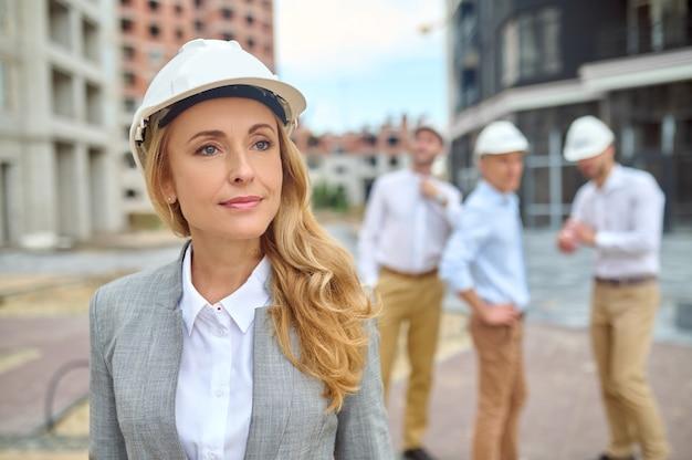 Ruhige attraktive weibliche inspektorin in einem bauarbeiterhelm, der im baubereich mit männlichen arbeitern im hintergrund steht