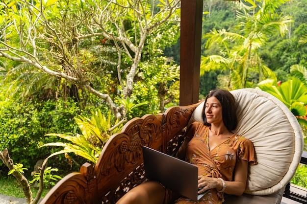 Ruhige aussicht. erfreutes brünettes mädchen, das ein lächeln auf ihrem gesicht behält, während sie grüne palmen betrachtet