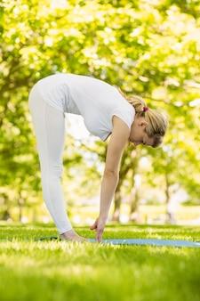 Ruhige blondine, die yoga im park tut